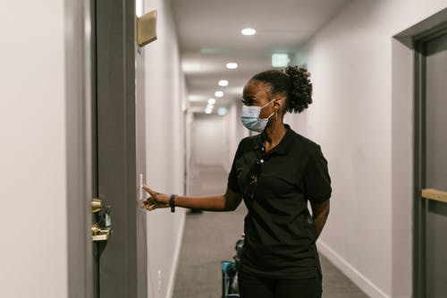 A Deliverywoman Pressing the Doorbell