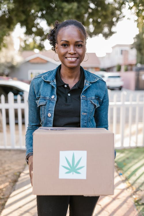 A Woman Carrying a Box with a Cannabis Leaf Sticker