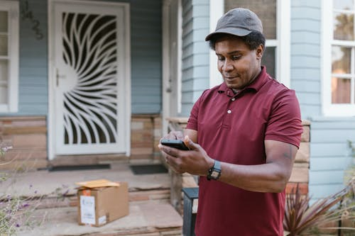 A Deliveryman Checking His Cellphone