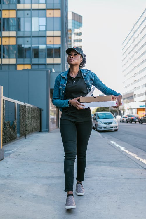 Woman in Blue Denim Jacket Standing on Sidewalk