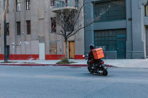 Man in Red Jacket Riding Motorcycle on Road