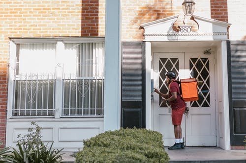 A Deliveryman Pressing the Doorbell