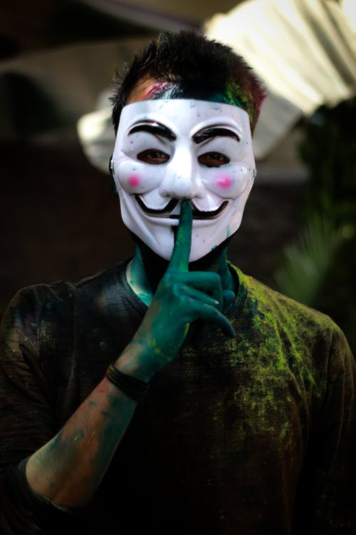 A Man Wearing a Mask and Covered with Colored Powders