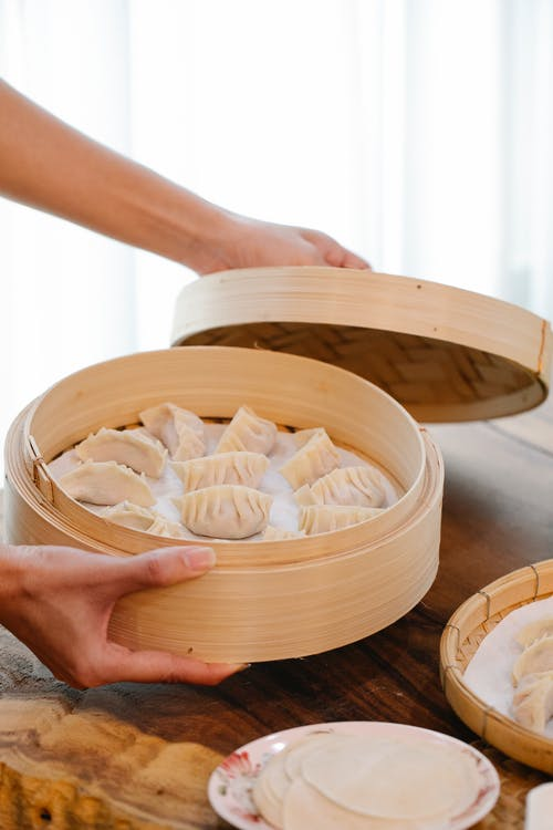 A Person Holding a Bamboo Steamer with Dumplings
