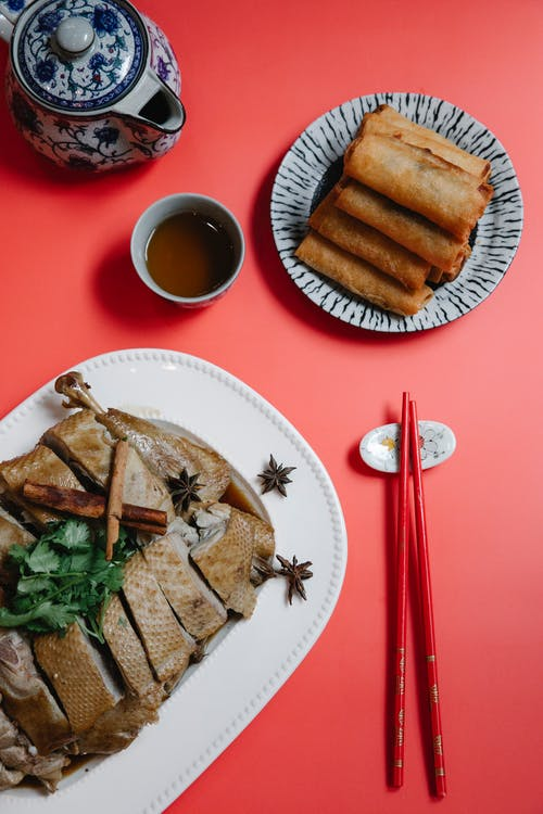 Delicious baked duck slices and spring rolls on red background
