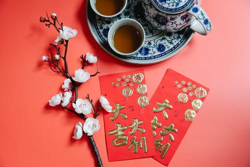 Top view of oriental packets with hieroglyphs against blossoming flower sprig and tea set during New Year holiday on red background