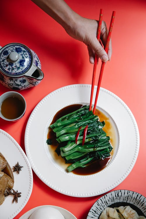 From above of crop unrecognizable person with chopsticks above tasty pak choi in soybean sauce against tea on red background