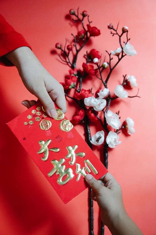 People Holding a Red Envelope