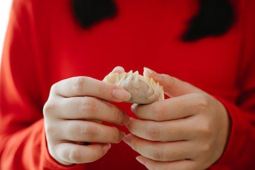 Crop faceless female folding traditional Asian jiaozi dumplings during dinner preparation in kitchen