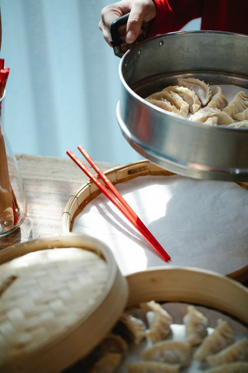 Anonymous woman putting pan with raw dumplings on table