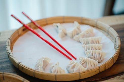 Raw dumplings with chopsticks on bamboo plate