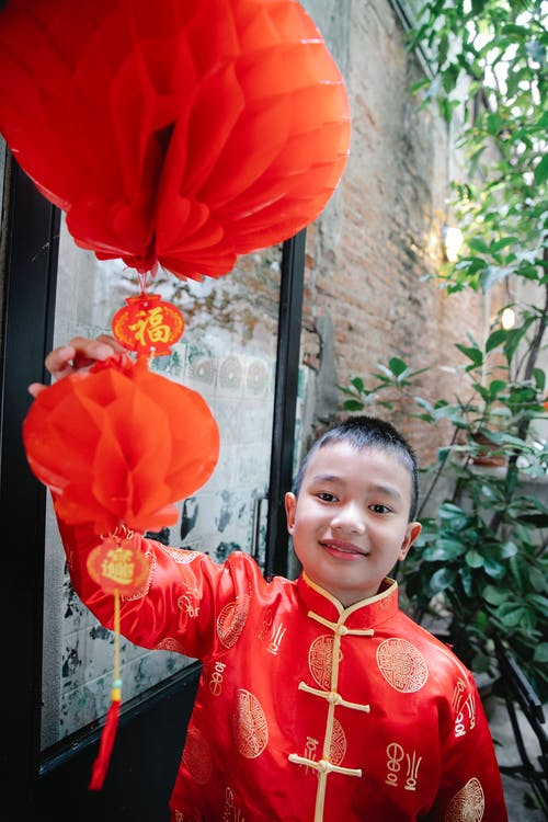 A Boy in Red Clothes Touching a Red Lantern