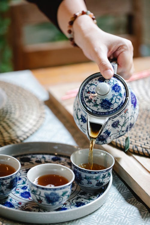 High angle of female pouring herbal tea into ceramic cups placed on tray for Chinese ceremony