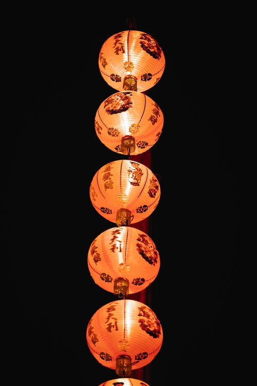 From below of decorative traditional Chinese lanterns with hieroglyphs and burning fire hanging on black sky