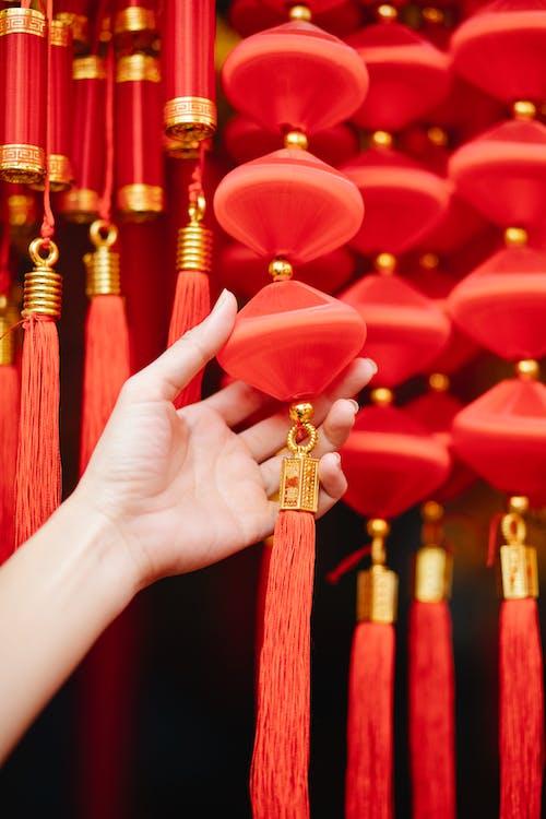 Woman touching red Chinese decorative lantern