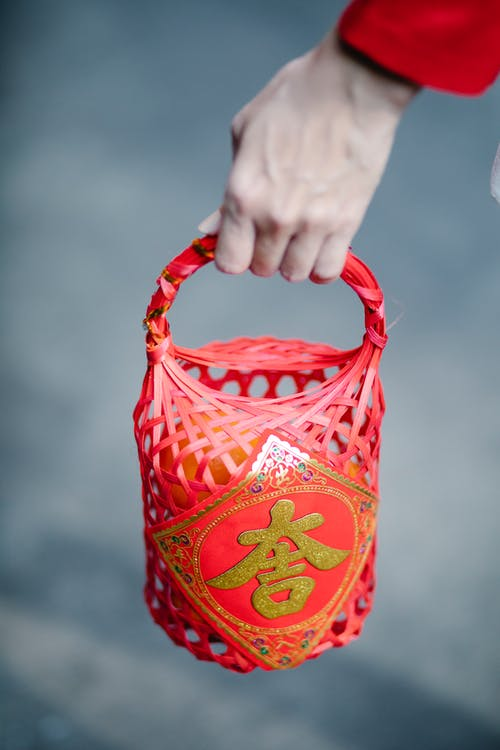 A Person Holding a Red Basket