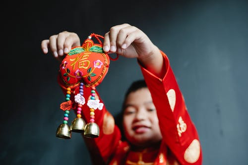 A Boy in Red Clothes Holding a Trinket