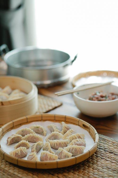 Dumplings on a Winnowing Basket and Bamboo Steamer