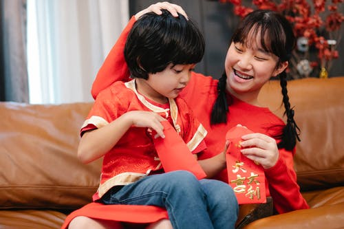 Siblings Spending Time Together while Holding Red Envelopes