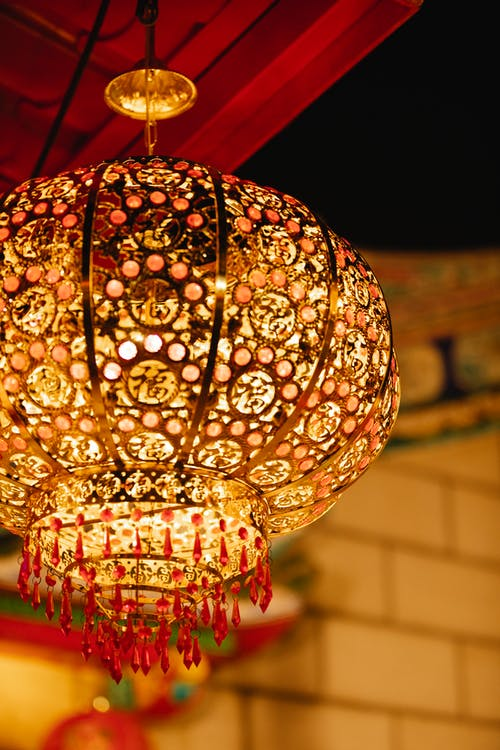 Low angle of traditional ornamental Asian lantern with glowing bulb hanging on street from ceiling of house against night sky during festive event