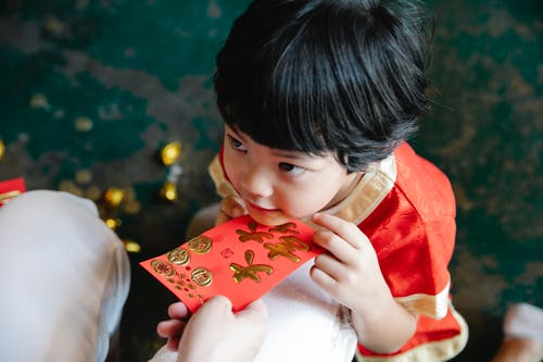 Crop mother giving hongbao red packet to son during New Year party
