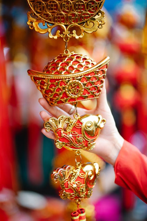Crop anonymous female touching traditional ornamental red and golden decoration with fish and sycee hanging in local street market during Chinese New Year holidays