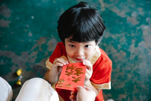 An Adult Giving a Red Envelope to a Young Boy