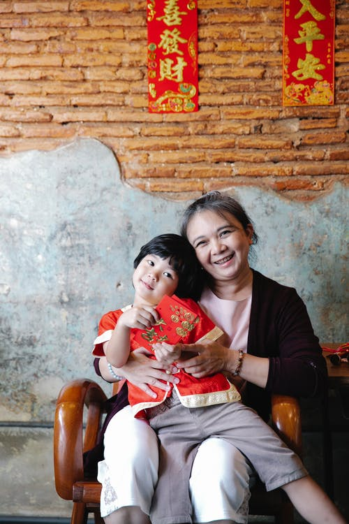 A Young Boy Sitting on the Lap of His Grandmother