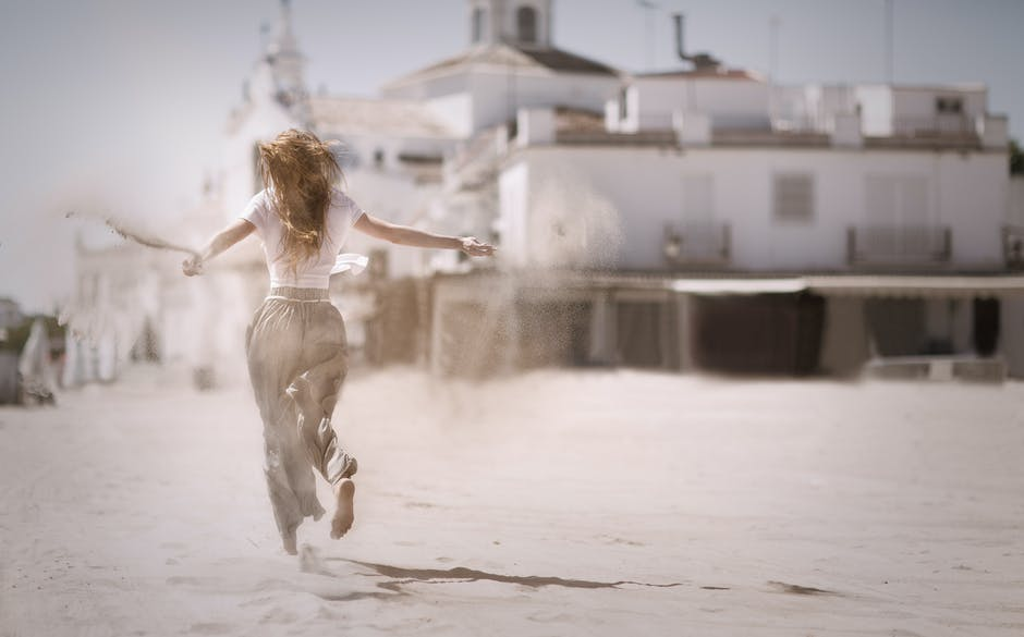 Woman Running on Sand Near White Concrete Building