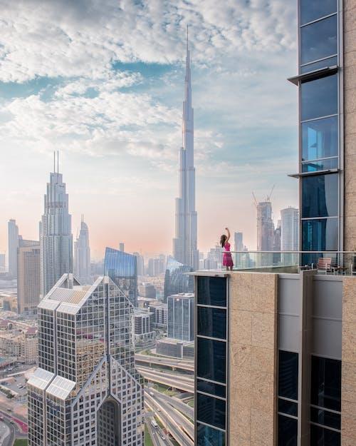 A Woman in a Pink Dress on a Skyscraper Balcony