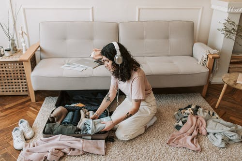 A Woman Listening on Her Headphones while Packing Her Clothes