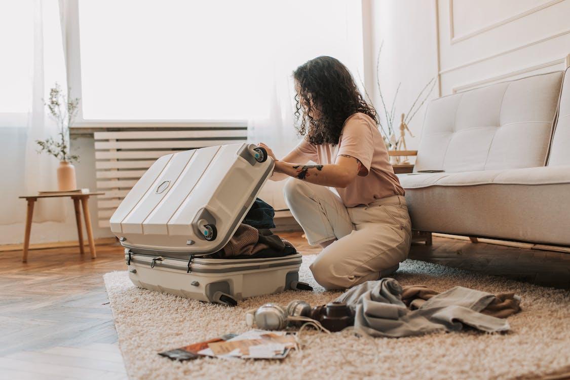 Woman in Beige Long Sleeve Shirt Sitting on Floor Using Gray Laptop Computer