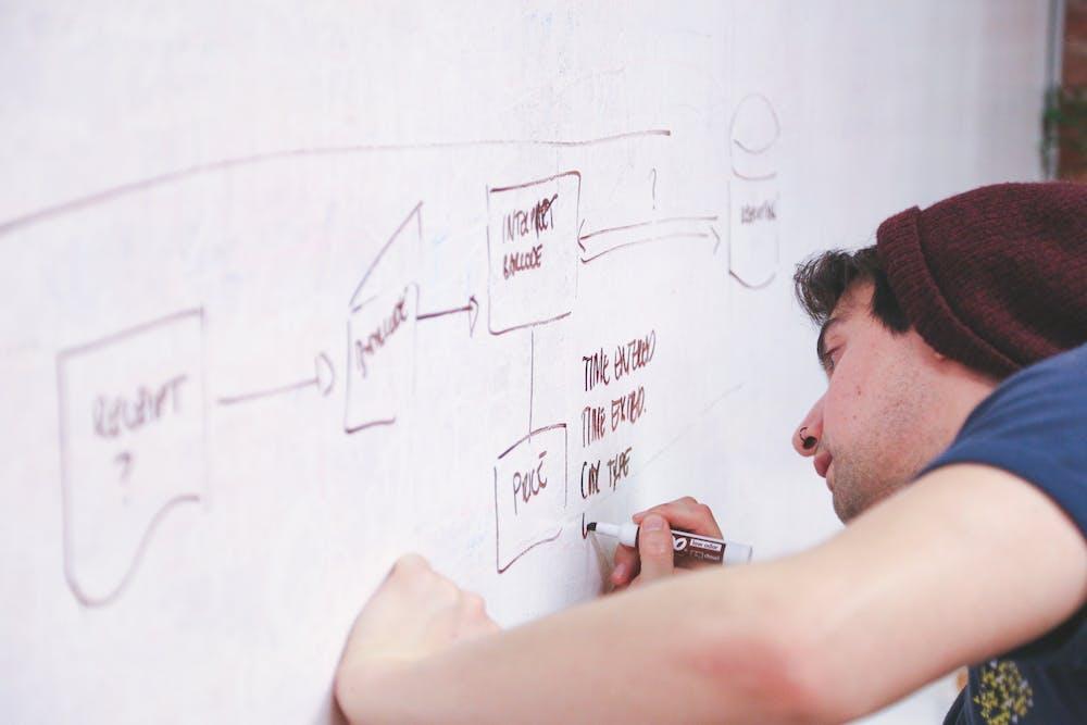 Teacher writing on the blackboard | Photo: Pexels