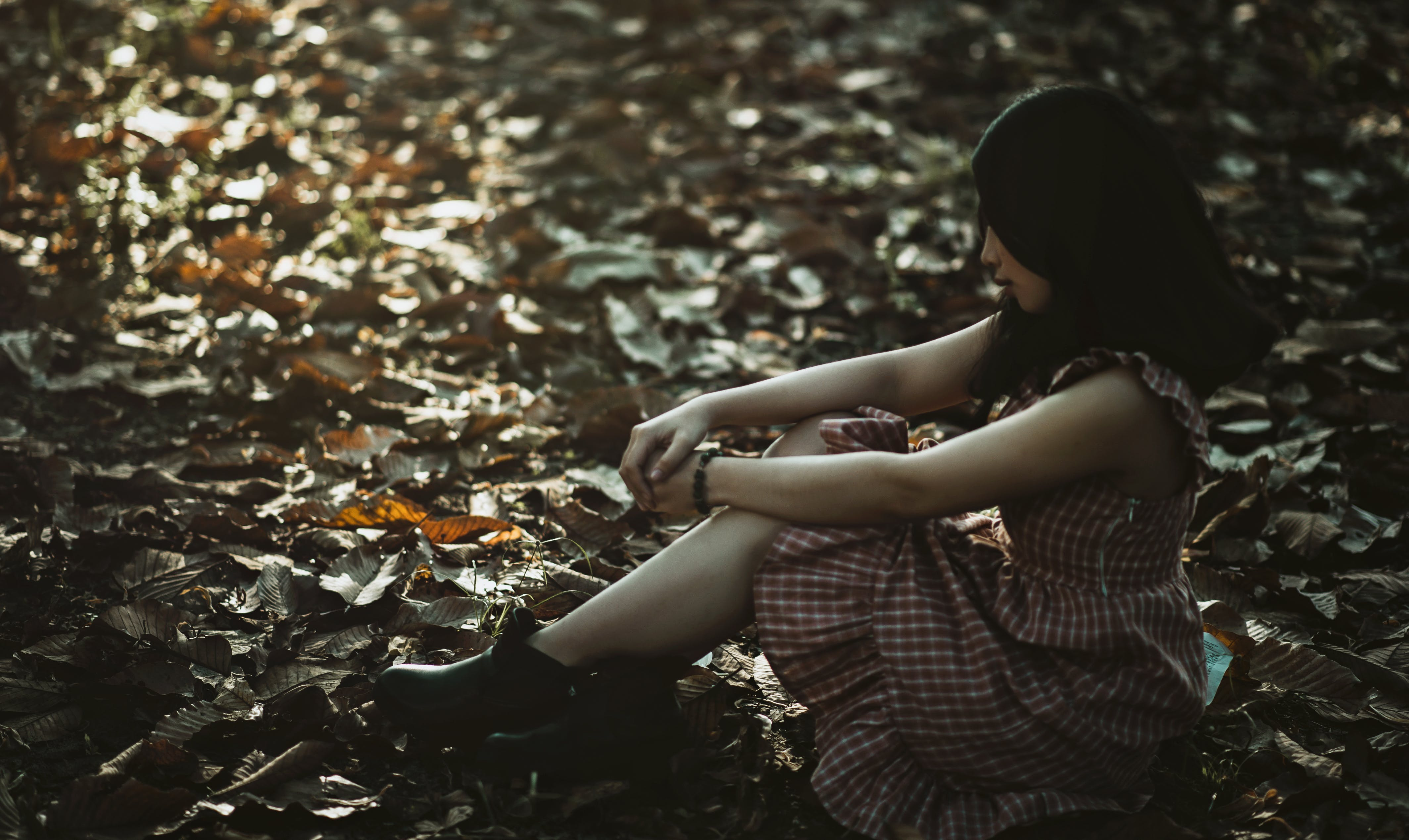 Photo of a Woman Sitting on the Ground Covered with Dried Leaves