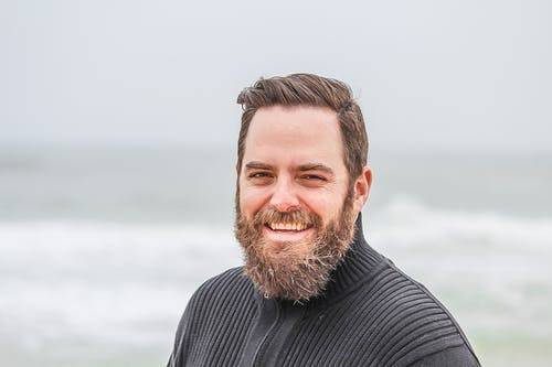 Man Wearing Black Zip-up Jacket Near Beach Smiling at the Photo