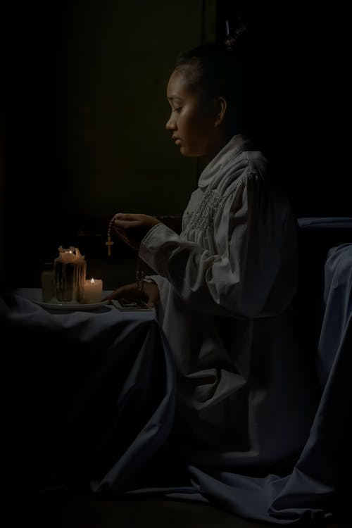 Side view of African American female teen in religious clothes with cross praying against flaming candles on black background
