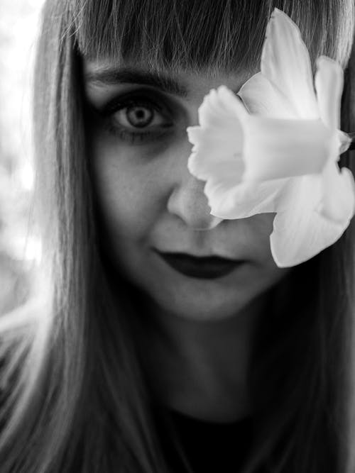 Grayscale Photo of Woman With White Flower on Her Ear
