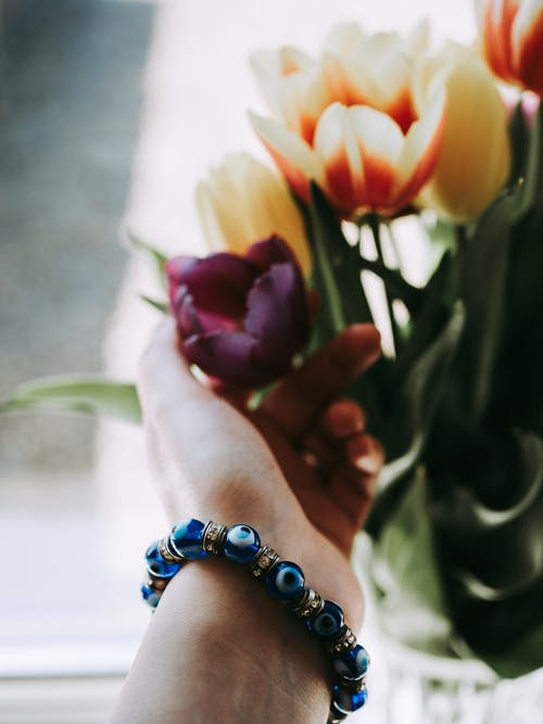 Person Wearing Blue and White Beaded Bracelet Holding Yellow and Pink Tulips