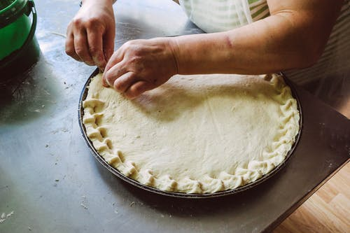 Person Holding Round Pie Dough on Grey Tray