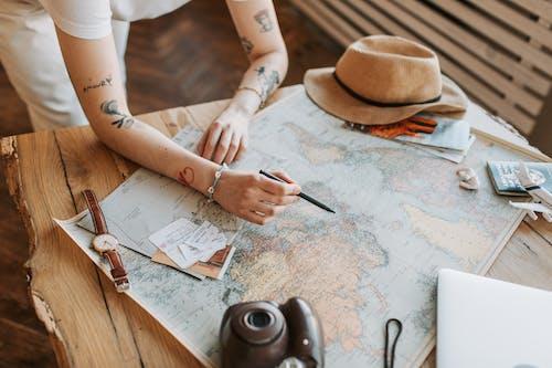 Photos gratuites de bras, carte du monde, chapeau