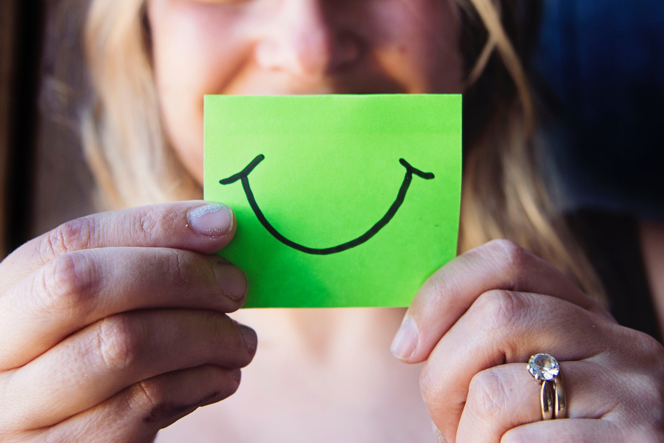 A woman holding a sticky note with a cartoon smile on it in front of her mouth