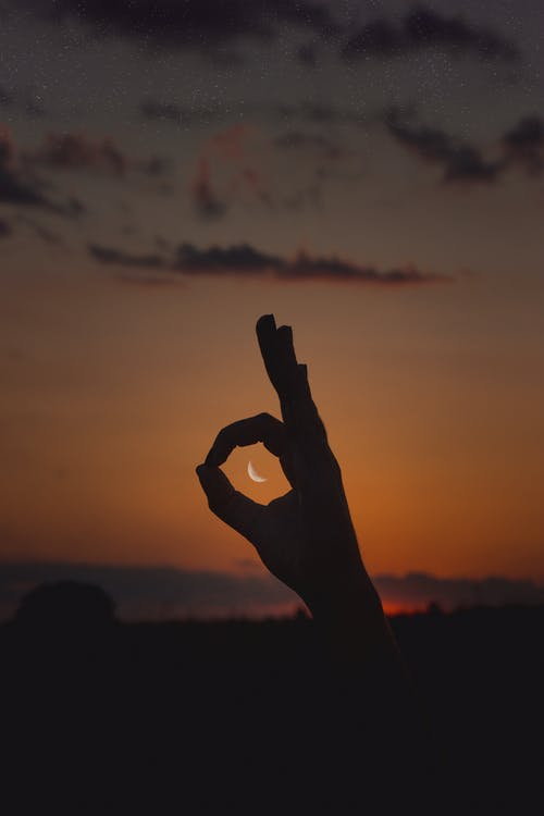 Silhouette of Person Raising Hand during Sunset