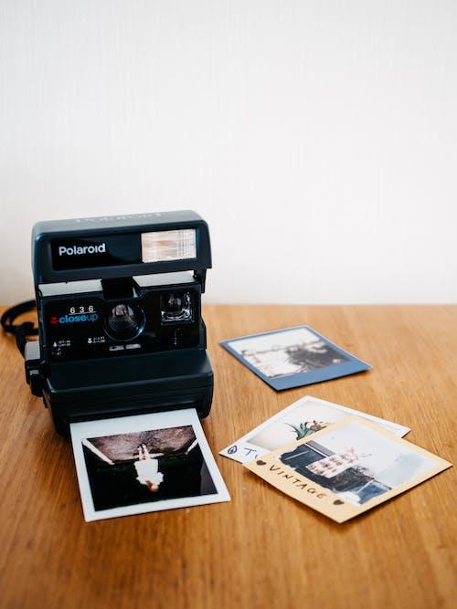 Black Polaroid Camera on Brown Wooden Table