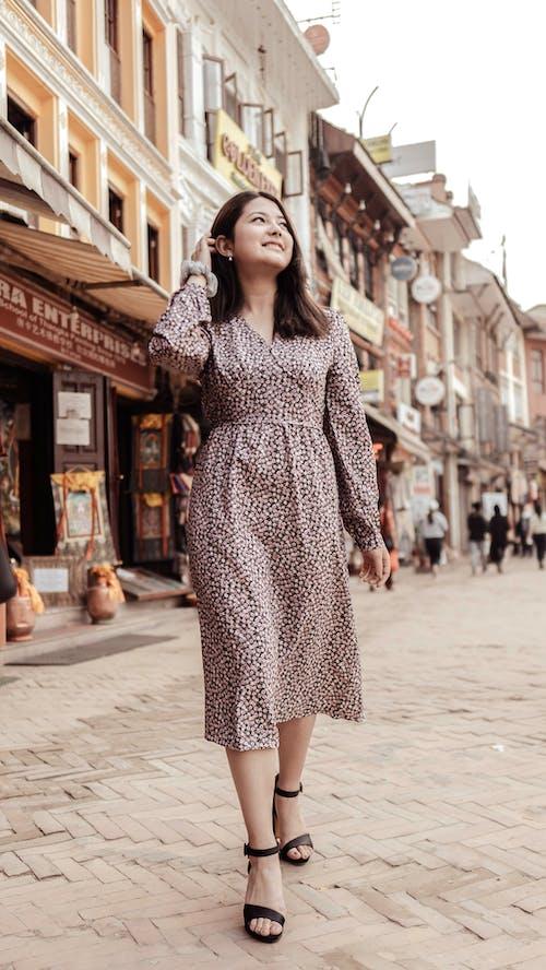 A Woman in Polka Dot Dress Walking in a Commercial Area