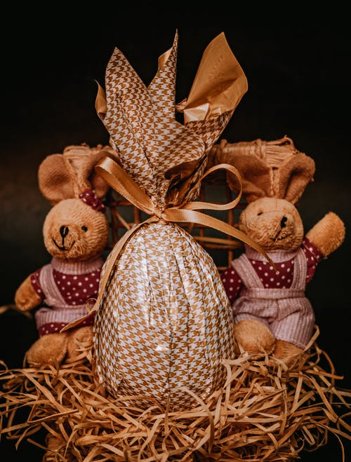 Wrapped chocolate Easter egg composed with toy rabbits