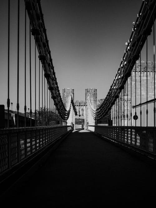 Grayscale Photo of Bridge With People Walking