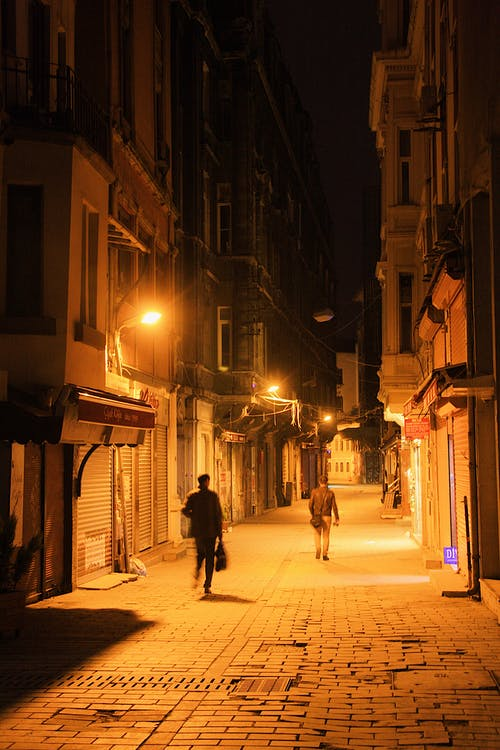 People walking on paved alley between old residential houses with glowing streetlights located on street at night time in city