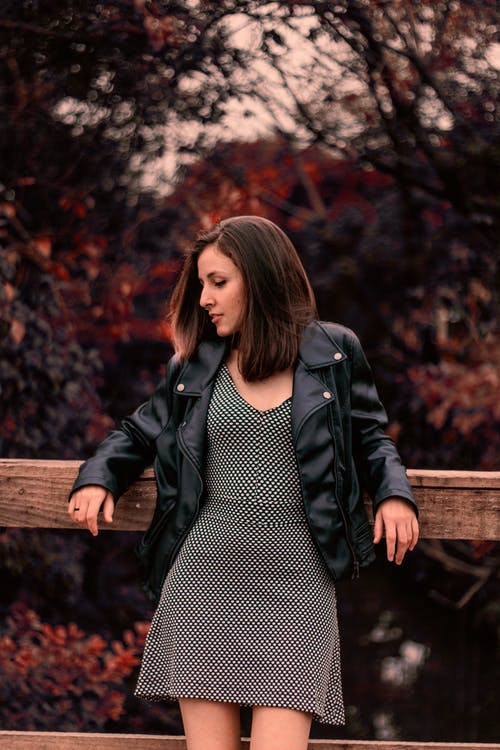 Woman in Black Leather Jacket Standing Near Brown Wooden Fence