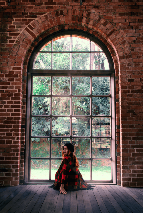 Woman in Red and Black Dress Standing in Front of Window