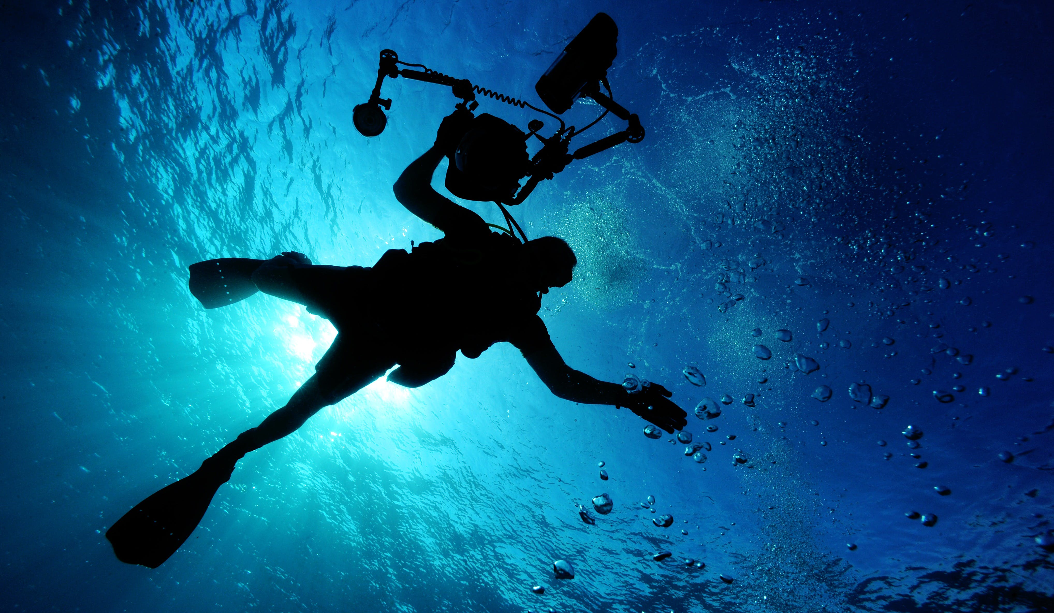 Silhouette of Person Holding Camera in Body of Water